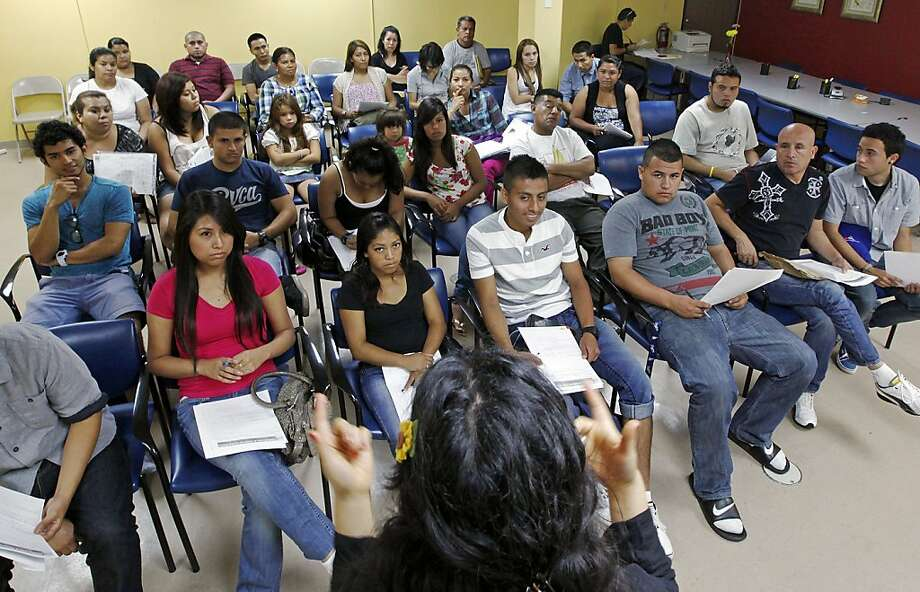 Immigrants attend an orientation seminar in Los Angeles, seeking to determine whether they qualify for work permits under the DACA program. Photo: Reed Saxon, Associated Press