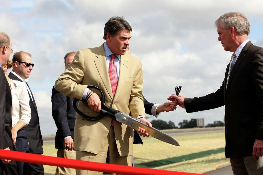 Texas Gov. Rick Perry carries the scissors during a ceremony for the opening of Texas 130 just west of Lockhart, Texas, Wednesday, Oct. 24, 2012. The toll road, which runs from IH-10 just east of Seguin, will connect with Texas 45, a toll road that circumvents Austin. Motorist will be able to drive 85-miles-per hour on Texas 130. To his right is Texas Transportation Commission Chairman Ted Houghton. Photo: Jerry Lara, San Antonio Express-News / © 2012 San Antonio Express-News