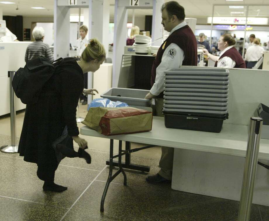 Laurie Manikowski takes off her boots before going through a security checkpoint on Dec. 21, 2002  at Seattle-Tacoma International Airport. Photo: JIM BRYANT, SEATTLE POST-INTELLIGENCER FILE