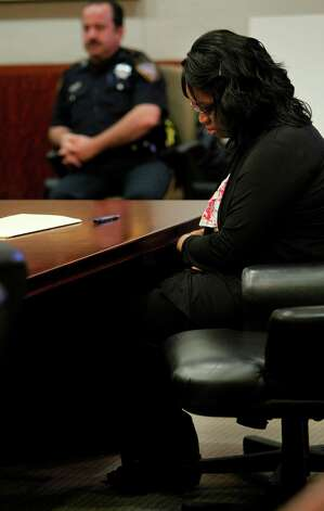 Jessica Tata, accused in the deaths of four children at her west Houston daycare, slumps over as she listens to defense attorney Mike Mike DeGeurin during opening statements at the Harris County Criminal Courthouse on Wednesday, Oct. 24, 2012, in Houston. Photo: Mayra Beltran, Houston Chronicle / © 2012 Houston Chronicle