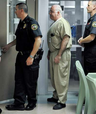 Michael Skakel, center, is brought to a holding area to await the decision of parole board during a hearing at McDougall-Walker Correctional Institution in Suffield, Conn., Wednesday, Oct. 24, 2012. Parole officials denied Skakel's first bid for parole since he was convicted a decade ago of killing his neighbor in 1975. Skakel is serving 20 years to life for fatally beating Martha Moxley with a golf club in Greenwich when they were 15-year-old neighbors. Photo: Jessica Hill, Jessica Hill/Associated Press / Greenwich Time contributed Associated Press