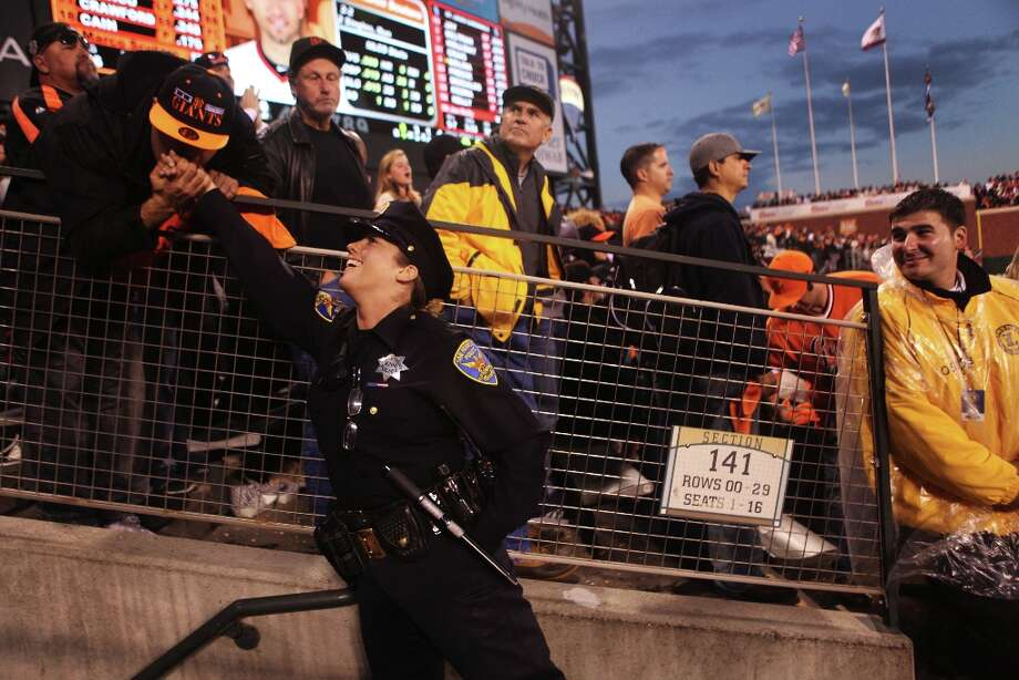 SFPD Officer Michelle Alvis receives a kiss on the hand from Giants fan Eddie Nazlou, of Santa Clara, after she gave him a high five, at right, James Adams, from Landmark Security, looks on during Game 7 of the NLCS between the San Francisco Giants and the St. Louis Cardinals at AT&T Park Monday, October 22, 2012 in San Francisco, Calif. Photo: Pete Kiehart, The Chronicle / ONLINE_YES