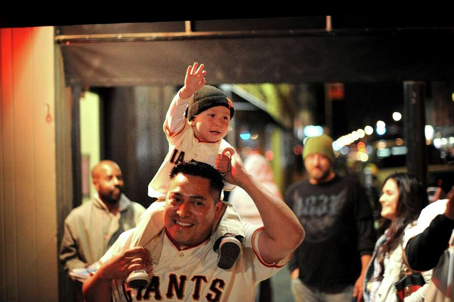 Wearing matching Buster Posey outfits, Enrique Escalante and his son Gabriel Escalante, 16  months, celebrate in the Mission as their team beats the Cardinals on Monday, Oct. 22, 2012, in San Francisco. Photo: Noah Berger, Special To The Chronicle / ONLINE_YES