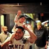 Wearing matching Buster Posey outfits, Enrique Escalante and his son Gabriel Escalante, 16  months, celebrate in the Mission as their team beats the Cardinals on Monday, Oct. 22, 2012, in San Francisco.