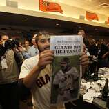 San Francisco  pitcher Sergio Romo displays a newspaper telling of their win  as they celebrate their victory over the St. Louis Cardinals 9-0 to win the NLCS Championship game at AT&T Park Monday, Oct. 22, 2012 in San Francisco, Calif.