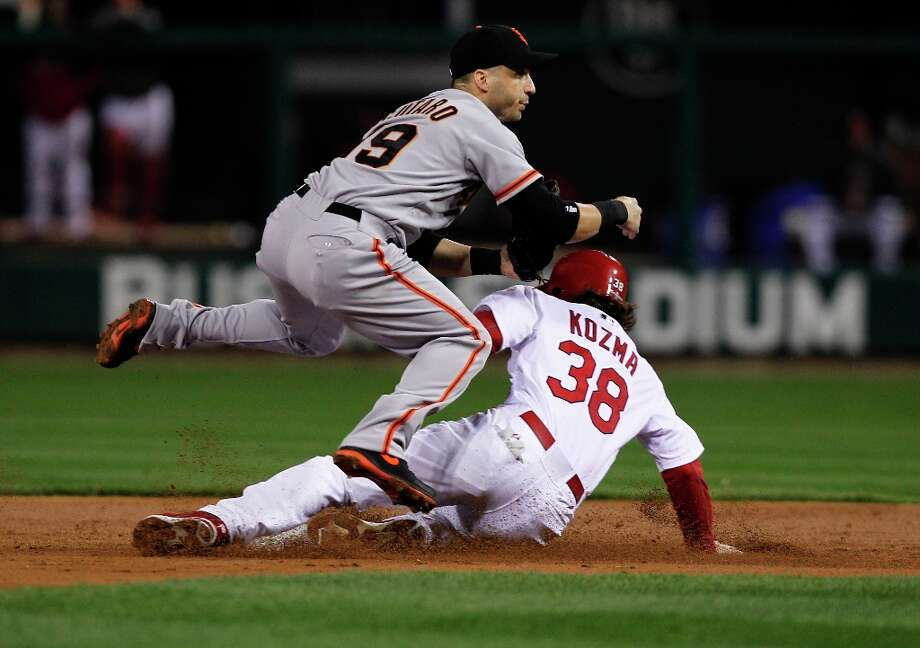 Giants' Marco Scutaro forces out the Cardinals' Pete Kozma and throws to complete a double play getting Lance Lynn at first base to end the second inning, as the San Francisco Giants take on the St. Louis Cardinals in game five of the National League Championship Series, on Friday Oct. 19, 2012 at Busch Stadium , in  St. Louis, Mo. Photo: Michael Macor, The Chronicle / ONLINE_YES