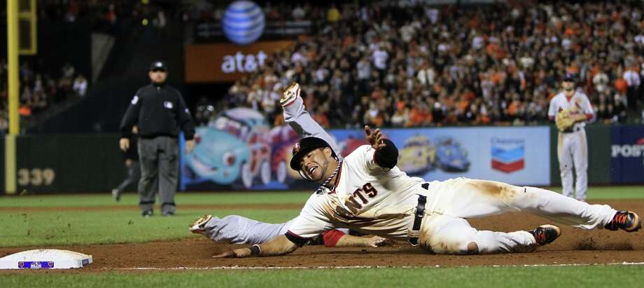 San Francisco Giants' Gregor Blanco dives safely back to first base past St. Louis Cardinals' Allen Craig on a fly ball by Brandon Crawford during the eighth inning in Game 2 of baseball's National League championship series against the San Francisco Giants on Monday, Oct. 15, 2012, in San Francisco. Photo: Chris Lee, Associated Press / St. Louis Post-Dispatch