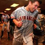 Giants' Buster Posey escapes a spray of champagne as the team celebrates in the clubhouse, as the San Francisco Giants beat the Cincinnati Reds 6-4 in game five to win the National League Division Series in Cincinnati, Ohio on Thursday Oct. 11, 2012.