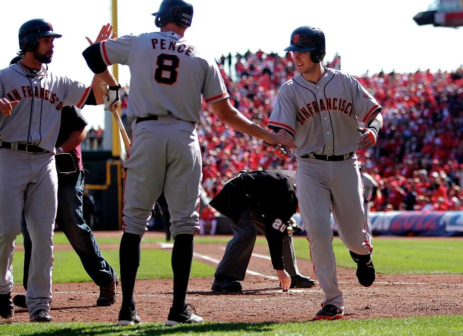 Giants' Angel Pagan and Hunter pence greet Buster Posey after his grand slam in the fifth inning,  as the San Francisco Giants went on to beat the Cincinnati Reds 6-4 in game five to win the National League Division Series in Cincinnati, Ohio on Thursday Oct. 11, 2012. Photo: Michael Macor, The Chronicle / ONLINE_YES