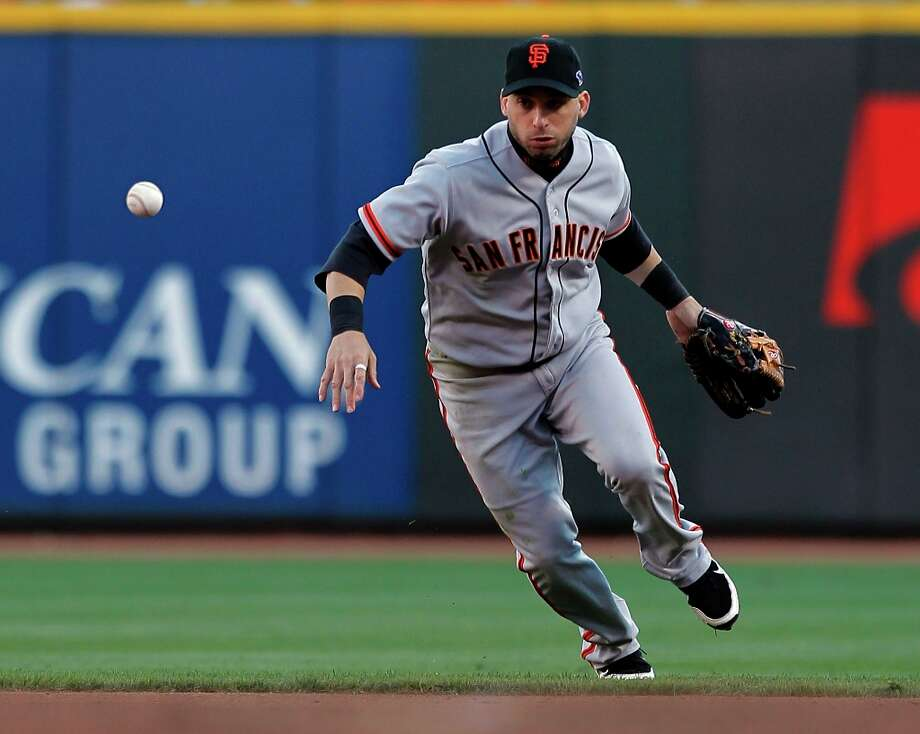 Giants second baseman Marco Scutaro has trouble handling a hit by the Reds Mike Leake in the fourth inning, as the San Francisco Giants  take on the Cincinnati Reds in game four of the National League Division Series in Cincinnati, Ohio on Wednesday Oct. 10, 2012. Photo: Michael Macor, The Chronicle / ONLINE_YES