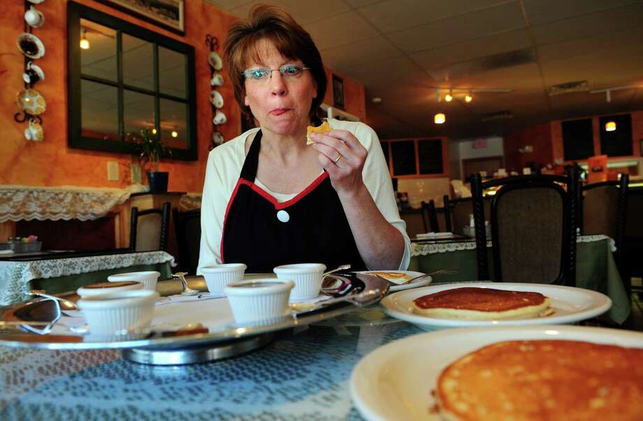 Lisa Stockbridge tastes different brands of maple-flavored syrup at Stockbridge's Gourmet Cheesecakes and Cafe in Shelton, Conn. (Autumn Driscoll/staff photographer)