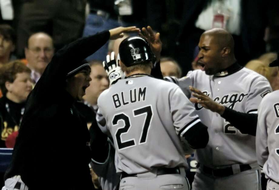 Chicago's Geoff Blum is congratulated by Jermaine Dye (right) and teammates after hitting a solo homer to give the White Sox a 6-5 lead in the 14th inning during Game 3. (Melissa Phillip / Chronicle)