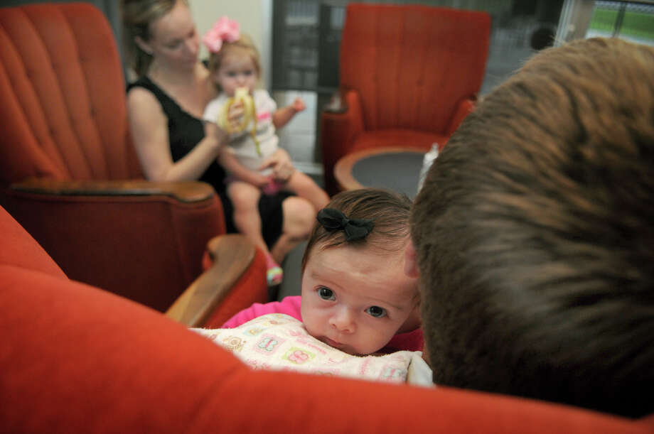 Zoey Ann Withers, 2 months, center, rests on the shoulder of her dad, Robert, 30, after finishing her bottle. Freelance photo by Jerry Baker Photo: Jerry Baker