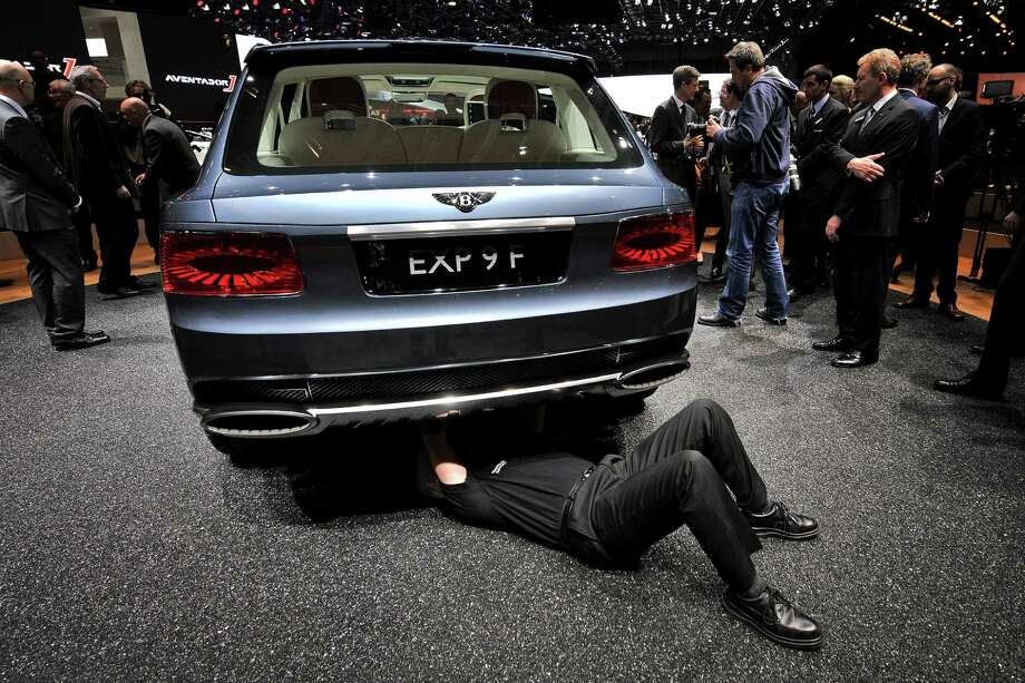 A technician works underneath the Bentley EXP 9 F concept car on March 6, 2012, during a press day ahead of the 82nd Geneva Car Show in Geneva. Photo: FABRICE COFFRINI, AFP/Getty Images / 2012 AFP