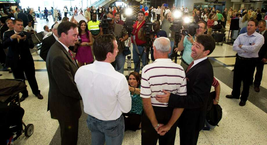 Kenny Chonoski, center left, and Carl Moody, center right, are surrounded by media upon their arrival. Rep. Pete Olson, R-Texas, left, and Roger Woolsey, CEO of American Jet International, flank the pilots. Photo: Brett Coomer, Houston Chronicle / Houston Chronicle