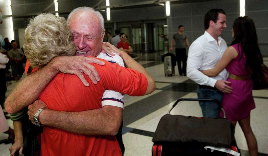 Carl Moody, left, embraces friend Nancy Kelly, as his co-pilot Kenny Chonosky is met by his fiance' Chelsie Brown, right, at George Bush Intercontinental Airport. Photo: Brett Coomer, Houston Chronicle / Houston Chronicle