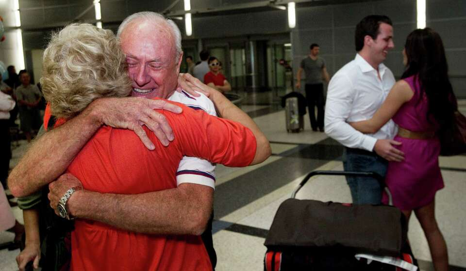 Carl Moody, left, embraces friend Nancy Kelly, as his co-pilot Kenny Chonosky is met by his fiance'