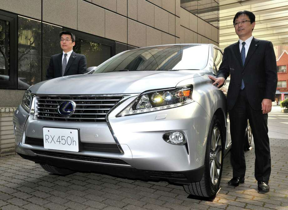 Moving to Japan, Toyota Motor managing officer Kazuo Ohara (right) introduces the company's newly designed Lexus RX hybrid SUV on April 12, 2012, in Tokyo.  Starting price: $45,910 for hybrid, $39,310 otherwise. Photo: YOSHIKAZU TSUNO, AFP/Getty Images / 2012 AFP
