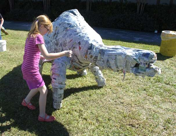 Madelynn Daniel, 9, of Lumberton, works on creating a papermache dinosaur on the lawn of the Texas Energy Museum during Dinosaur Day on Saturday. Valentino Mauricio/The Enterprise Photo: Valentino Mauricio / Beaumont