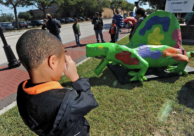 Jay Francis, 9, photographs a Papier-mâché dinosaur at The Energy Museum's recent Dinosaur Days event in Downtown Beaumont. Guiseppe Barranco/The Enterprise