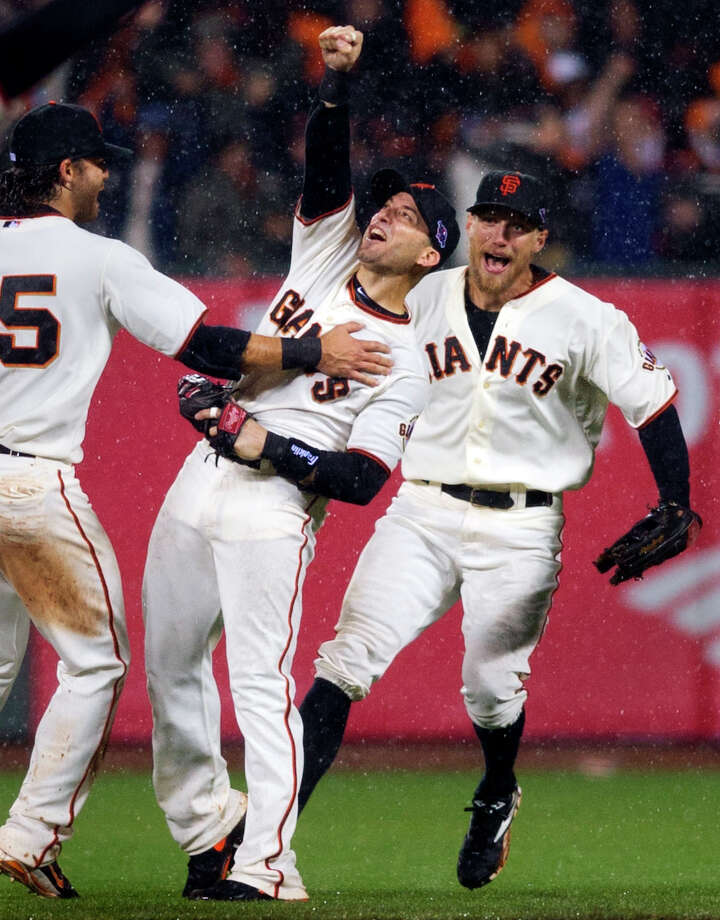 San Francisco Giants' Marco Scutaro, center, celebrates with Hunter Pence, right, and Brandon Crawford after Scutaro made the final out of Game 7 of baseball's National League championship series against the St. Louis Cardinals, Monday, Oct. 22, 2012, in San Francisco. The Giants won 9-0. Photo: Randy Pench / Associated Press / The Sacramento Bee