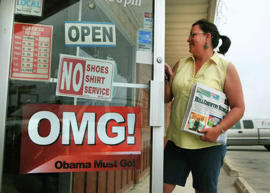 "Julie Becker, Editor and Publisher of The Hill Country Herald in Leakey, TX, drops off a stack of the latest edition at Hill Country Bar-B-Que Restaurant.  The restaurant, owned by Shawna Romo, proudly posted the sign ""Obama Must Go"", on the front door. Most people in the town of Leakey think nothing of the sign Pastor Ray Miller put on his church, Church in the Valley, two weeks ago which read ""Vote for the Mormon, Not the Muslim"". Becker said she wouldn't report on anything Miller says.  Wednesday, Oct. 24, 2012. Photo: Bob Owen, San Antonio Express-News / San Antonio Express-News"