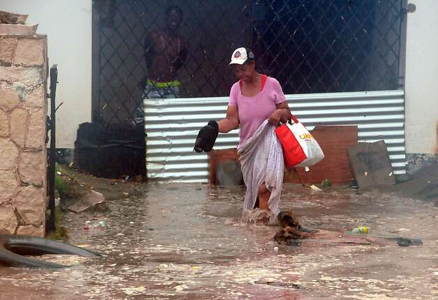 A woman wades through flood water brought by Hurricane Sandy as she evacuates her home in the Caribbean Terrace neighborhood of eastern Kingston, Jamaica, Wednesday, Oct. 24, 2012.  Hurricane Sandy pounded Jamaica with heavy rain as it headed for landfall near the country's most populous city on a track that would carry it across the Caribbean island to Cuba, and a possible threat to Florida.  (AP Photo/Collin Reid) Photo: Collin Reid, Associated Press