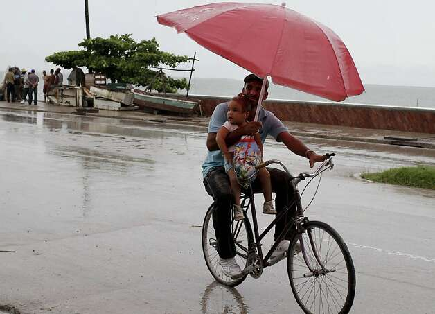 A man balances a child and umbrella on his bike as it rains during the approach of Hurricane Sandy in Manzanillo, Cuba, Wednesday, Oct. 24, 2012. Hurricane Sandy pounded Jamaica with heavy rain as it headed for landfall near the country's most populous city on a track that would carry it across the Caribbean island to Cuba, and a possible threat to Florida. (AP Photo/Franklin Reyes) Photo: Franklin Reyes, Associated Press