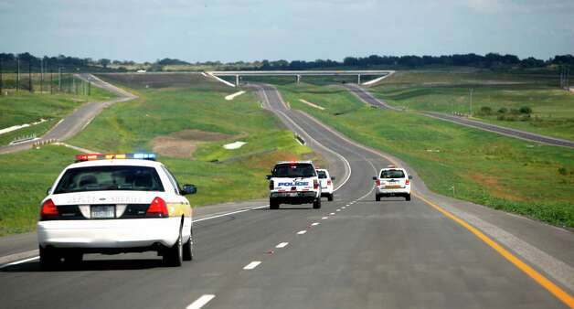 Work crews and police cars drive north bound Wednesday afternoon Oct. 24, 2012 on the south bound lanes of the southern extension of Texas 130 between Seguin and Austin as they open the road behind them. The road has the highest speed limit--85 mph--of any road in the country. Photo: William Luther, San Antonio Express-News / © 2012 San Antonio Express-News