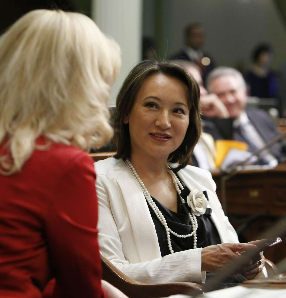 FILE - In this Jan. 4, 2012 file photo, Assemblywoman Mary Hayashi, D-Hayward, right, talks with her seat mate, Assemblywoman Cathleen Galgiani, D-Ceres, at the Capitol in Sacramento, Calif. An examination of lawmakers' voting records by the Associated Press found that Hayashi changed or added votes on legislation 291 times, more than any other member of the Assembly, while Galgiani changed her votes 139 times. The California Assembly is one of 10 state legislative bodies nationwide that allow lawmakers to change the official records for how they acted on specific pieces of legislation. (AP Photo/Rich Pedroncelli, File)