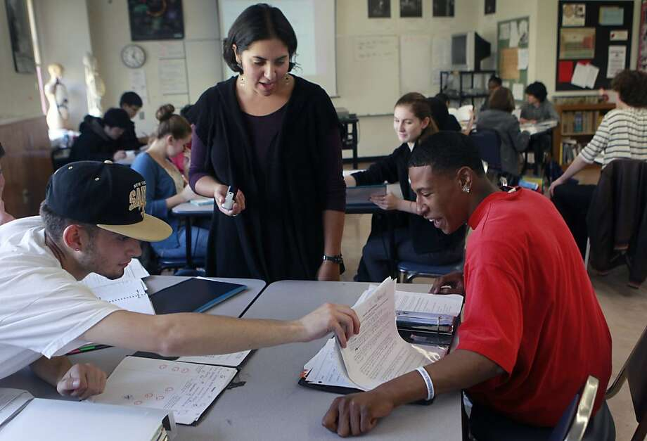 Biology teacher Amanda Goldman at S.F.'s Gateway High School checks assignments with Jake D'Amato (left) and Elijah Hill. Photo: Paul Chinn, The Chronicle