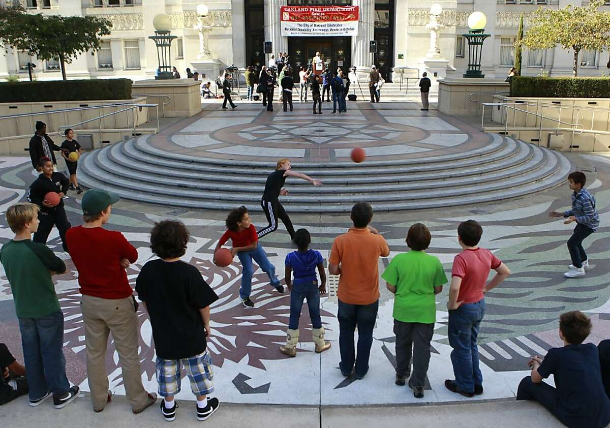Students from the Oakland School for the Arts play a game of dodge ball on Frank Ogawa Plaza before a news conference by city officials and business leaders (background) to talk about downtown Oakland's renaissance during the past year on the steps of City Hall in Oakland, Calif. on Wednesday, Oct. 24, 2012. Thursday marks the one-year anniversary of the Occupy Oakland movement.