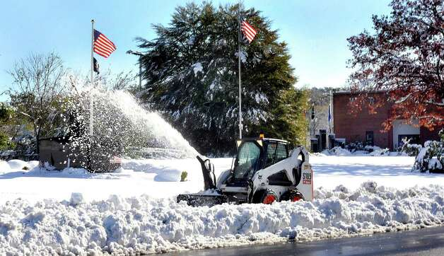 A snowplow clears the front of the War Memorial in Danbury, Sunday, Oct. 30, 2011. The Danbury area had a major snowstorm last year, just before Halloween. Photo: Michael Duffy