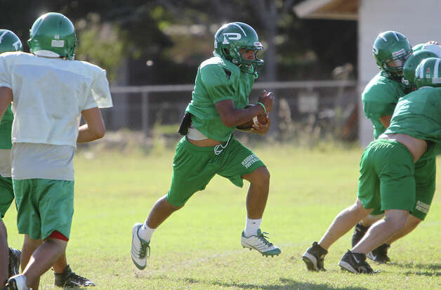 Pleasanton High School junior running back Jacob Arevalo (center) practices with the team on Wednesday, Oct. 24, 2012. The Eagles are 8-0 this season after going 2-8 last year. Head coach Tab Dumont said Arevalo has helped the Eagles improve their running game from last season. Photo: Kin Man Hui, San Antonio Express-News / San Antonio Express-News