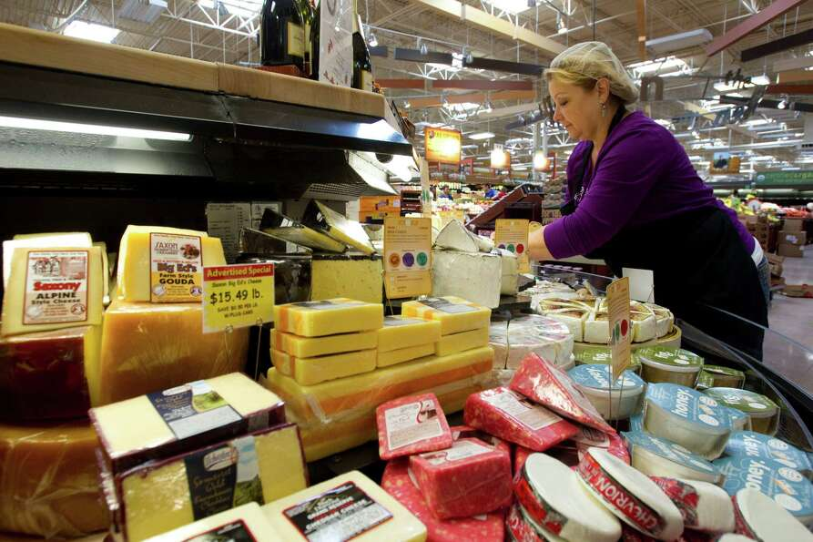 Melissa Lamey sets up the cheese display at the new Kroger on Studemont Wednesday, Oct. 24, 2012, in