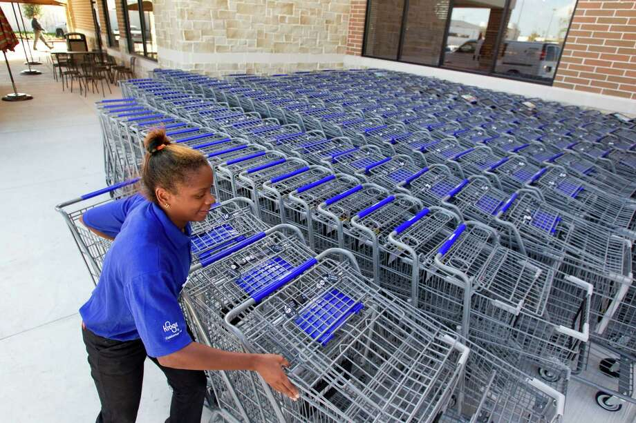 Serreva Vincent-Batiste gathers carts outside the new Kroger on Studemont Wednesday, Oct. 24, 2012, in Houston. The signature grocery store is scheduled to open October 26. Photo: Brett Coomer, Houston Chronicle / © 2012 Houston Chronicle