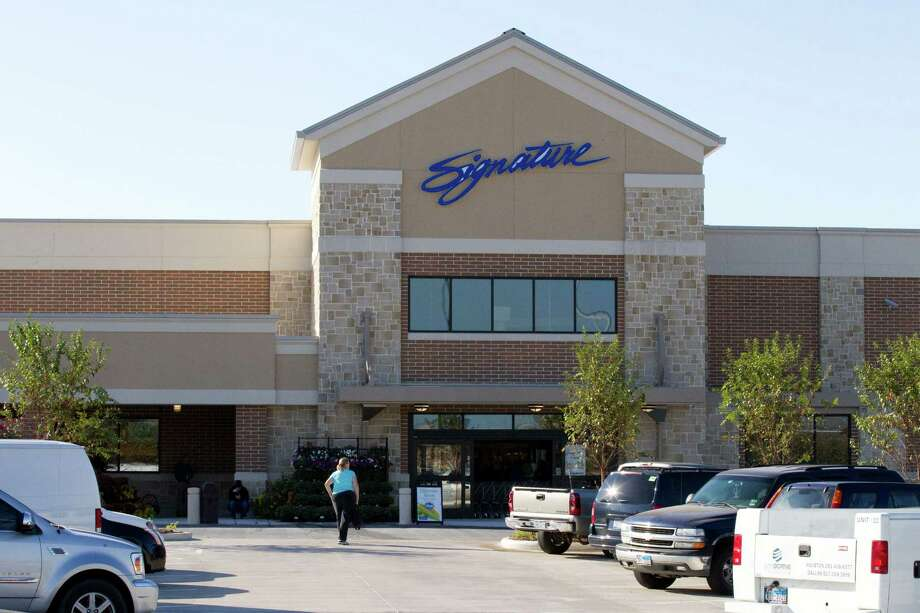 A woman walks toward the doors at the new Kroger on Studemont Wednesday, Oct. 24, 2012, in Houston. The signature grocery store is scheduled to open October 26. Photo: Brett Coomer, Houston Chronicle / © 2012 Houston Chronicle