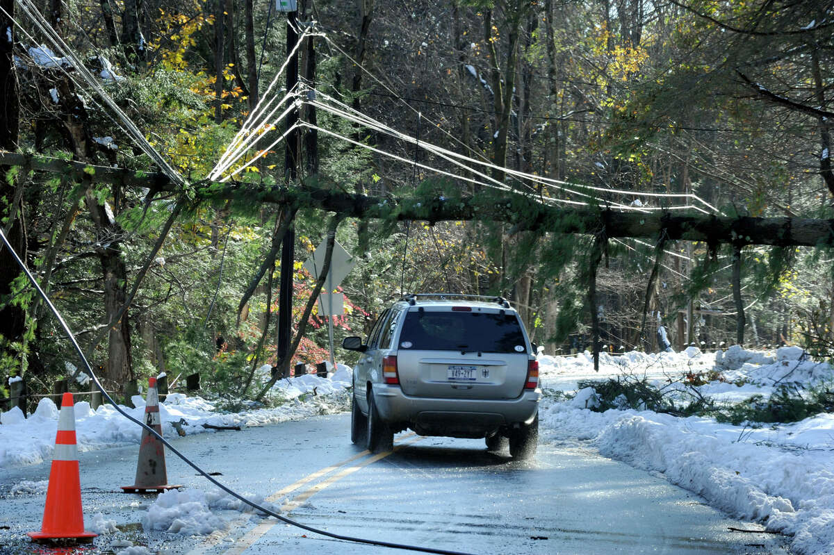 Tree branches rest on wires on Route 37 in Sherman, Conn. on Sunday, Oct. 30, 2011 after a heavy overnight snowfall.