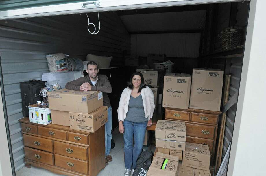 Corey Miglucci and his wife, Deserae Miglucci stand at the storage unit on Wednesday, Oct. 24, 2012 in East Greenbush, NY.  The Miglucci's were all set to move into an apartment complex last weekend, only to find that their apartment was not ready and then they had to rush to find a storage unit to take their belongings as they try to find a place to live.    (Paul Buckowski / Times Union) Photo: Paul Buckowski