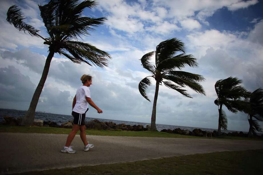 Stephanie Bilyeu walks along the ocean as blustery winds blow through the palm trees as the outerbands of Hurricane Sandy are felt on October 24, 2012 in Miami, Florida. Photo: Joe Raedle, Getty Images / 2012 Getty Images