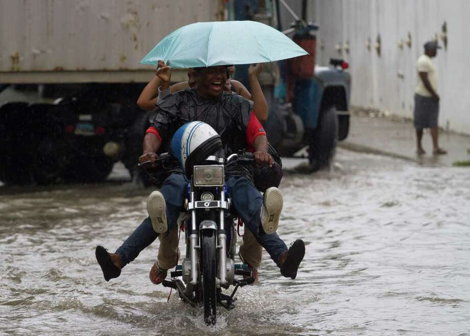 Locals ride a motorbike in a flooded street of Santo Domingo before the arrival of Hurricane Sandy on October 24, 2012. The category one hurricane on the five-level Saffir-Simpson scale was forecast to dump up to 12 inches of rain across Jamaica, Haiti, the Dominican Republic, Haiti and eastern Cuba. Photo: ERIKA SANTELICES, AFP/Getty Images / afp