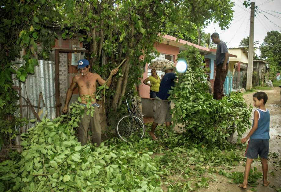 "Citizens of Bayamo, 740 km east of Havana, prune trees on October 24, 2012 as the residents of eastern Cuba prepare for the arrival of Hurricane Sandy. Hurricane conditions were expected in eastern Cuba in the evening, with the storm set to pass over the Bahamas Thursday and Friday, according to the NHC, which warned that conditions were ""deteriorating"" in Jamaica. Photo: STR, AFP/Getty Images / AFP"