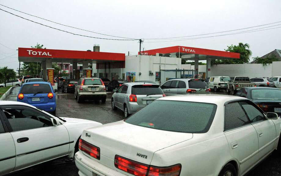 Drivers wait to fill their cars with fuel as rain brought by the outer bands of Tropical Storm Sandy fall in Kingston, Jamaica, Tuesday, Oct. 23, 2012. The U.S. National Hurricane Center in Miami said Sandy was expected to become a hurricane as it nears Jamaica on Wednesday. Photo: Collin Reid, Associated Press / AP