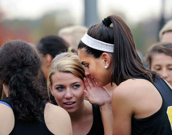 At right, Lexie Hearn of Greenwich Academy whispers to a teammate before the start of the high school cross country meet at Brunswick School in Greenwich, Wednesday, Oct. 24, 2012. Photo: Bob Luckey / Greenwich Time