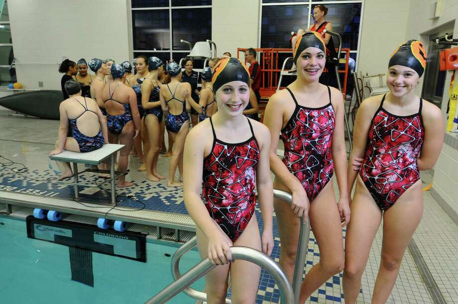 Kylie George, left, Sierra Carlstadt, center, and Emma Brown are the only members of the Scotia-Glenville High School swim team, which is self-funded due to budget cuts. Their last home meet was held at Schenectady High School on Tuesday Oct. 23, 2012 in Schenectady, NY.  The three have all qualified for the sectionals.  The 16 members of the Schenectady High School girls swim team gather behind them at left. (Philip Kamrass /  Times Union) Photo: Philip Kamrass / 10019777A