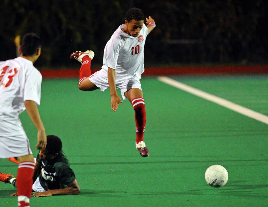 Central's #10 Nelite Soares leaps over a Bassick player while chasing down the ball, during boys soccer action in Bridgeport, Conn. on Wednesday October 24, 2012. Photo: Christian Abraham