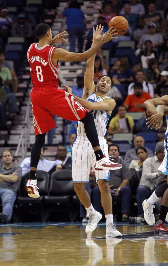 Houston Rockets point guard Shaun Livingston (8) passes around New Orleans Hornets point guard Greivis Vasquez (21) in the second half of a preseason NBA basketball game in New Orleans, Wednesday, Oct. 24, 2012. The Rockets won 97-90. (AP Photo/Gerald Herbert) (Associated Press)