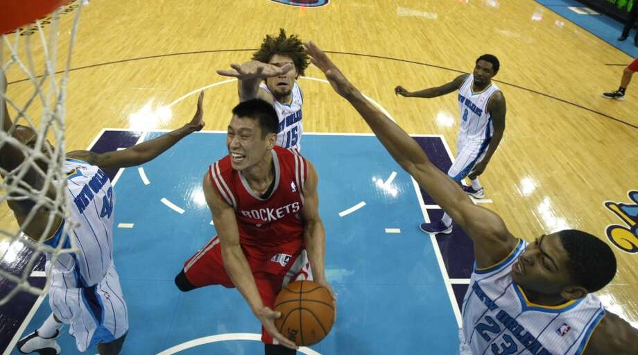 Houston Rockets point guard Jeremy Lin, center front, drives to the basket between New Orleans Hornets small forward Lance Thomas (42), center Robin Lopez (15) and power forward Anthony Davis (23) in the first half of a preseason NBA basketball game in New Orleans, Wednesday, Oct. 24, 2012. (AP Photo/Gerald Herbert) (Associated Press)