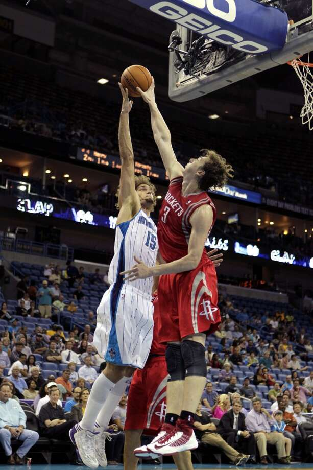 Houston Rockets center Omer Asik (3) blocks a shot by New Orleans Hornets center Robin Lopez (15) in the second half of a preseason NBA basketball game in New Orleans, Wednesday, Oct. 24, 2012. The Rockets won 97-90. (AP Photo/Gerald Herbert) (Associated Press)