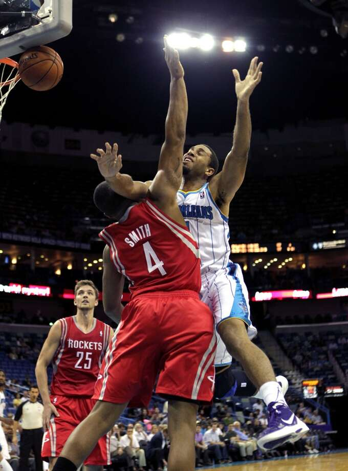 New Orleans Hornets shooting guard Xavier Henry, right, battles for a loose ball against Houston Rockets power forward Greg Smith (4) in the second half of a preseason NBA basketball game in New Orleans, Wednesday, Oct. 24, 2012. The Rockets won 97-90. (AP Photo/Gerald Herbert) (Associated Press)